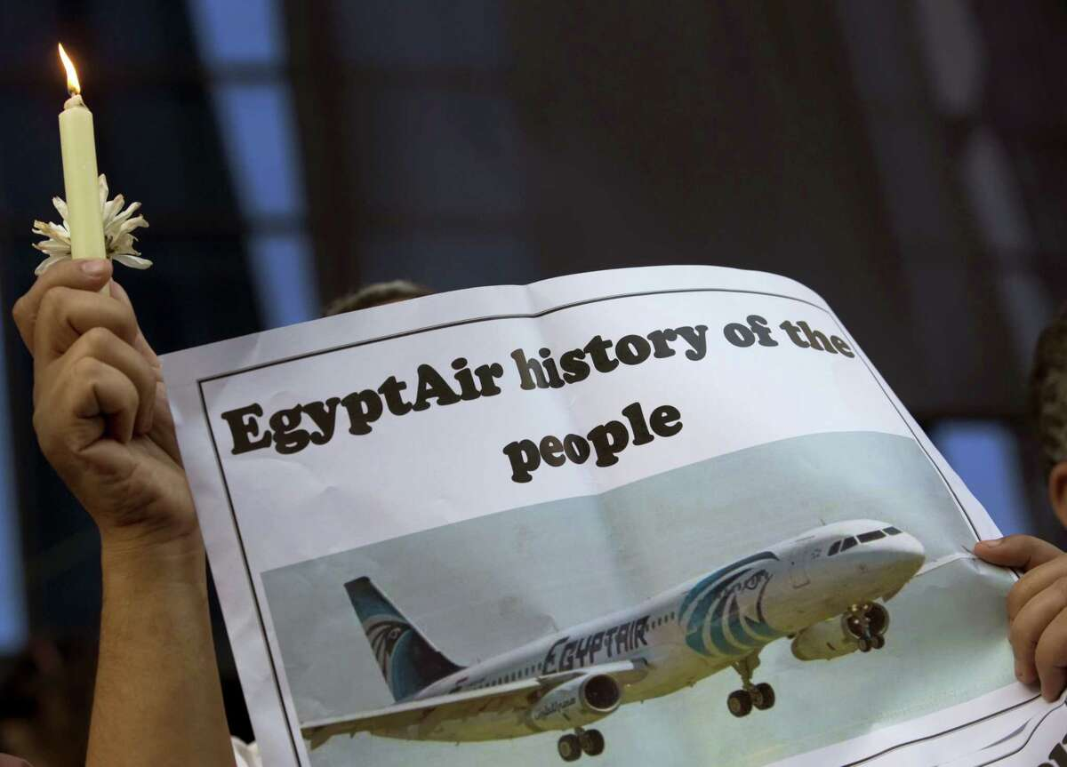 In this May 24, 2016 photo, an Egyptian journalist holds a candle and a poster supporting EgyptAir during a candlelight vigil for the victims of EgyptAir flight 804 in front of the Journalists' Syndicate in Cairo, Egypt. Egypt on Wednesday, June 15, 2016 said that it spotted and obtained images from the wreckage of the EgyptAir plane flying from Paris to Cairo that crashed into the Mediterranean last month, killing all 66 people on board, according to a statement by the country's investigation committee.