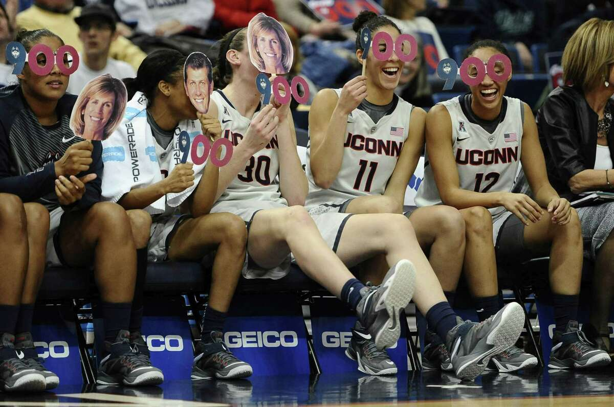 UConn players share a light moment on the bench on a night when coach Geno Auriemma won his 900th game.