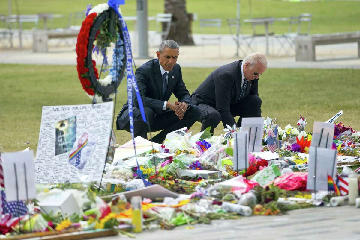 President Barack Obama and Vice President Joe Biden visit a memorial to the victims of the Pulse nightclub shooting, Thursday, June 16, 2016 in Orlando, Fla. Offering sympathy but no easy answers, Obama came to Orlando to try to console those mourning the deadliest shooting in modern U.S history.
