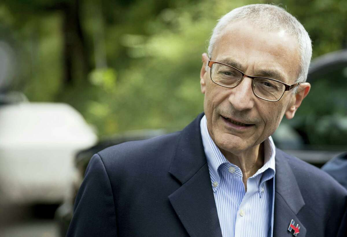 In this photo taken Oct. 5, 2016, file photo, Hillary Clinton's campaign manager John Podesta speaks to members of the media outside Democratic presidential candidate Hillary Clinton's home in Washington. Hacked emails reveal internal disagreement among top Clinton aides about her determination to hold a Clinton Foundation summit in Morocco that later drew attention over its reliance on large donations from foreign governments.