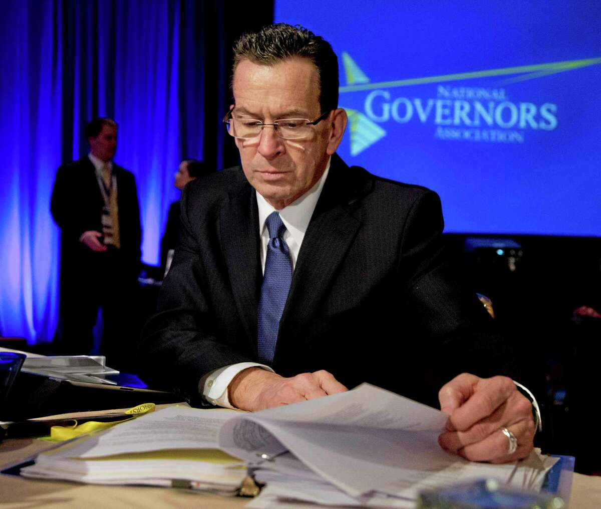Connecticut Gov. Dannel P. Malloy reads documents during the National Governors Association 2013 Winter Meeting in Washington on Feb. 23, 2013.