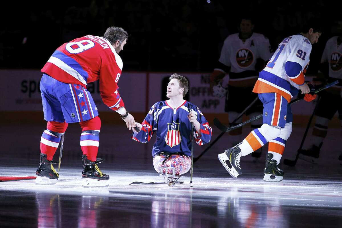 US Marine Corps Lance Corporal Joshua Misiewicz, a member of the USA National sled hockey team, gets a puck from Washington Capitals left wing Alex Ovechkin (8), from Russia, after a pre-game ceremonial puck drop with New York Islanders center John Tavares (91) before an NHL hockey game, Thursday, Feb. 4, 2016, in Washington. (AP Photo/Alex Brandon)