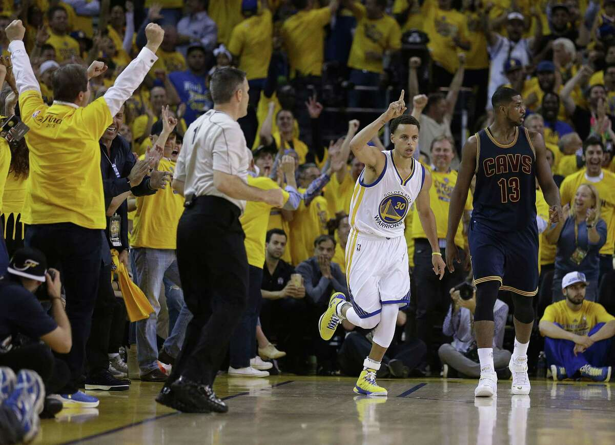 Warriors guard Stephen Curry, center, reacts after scoring in front of Cavaliers center Tristan Thompson during the first half of Game 1 of the NBA Finals on Thursday.