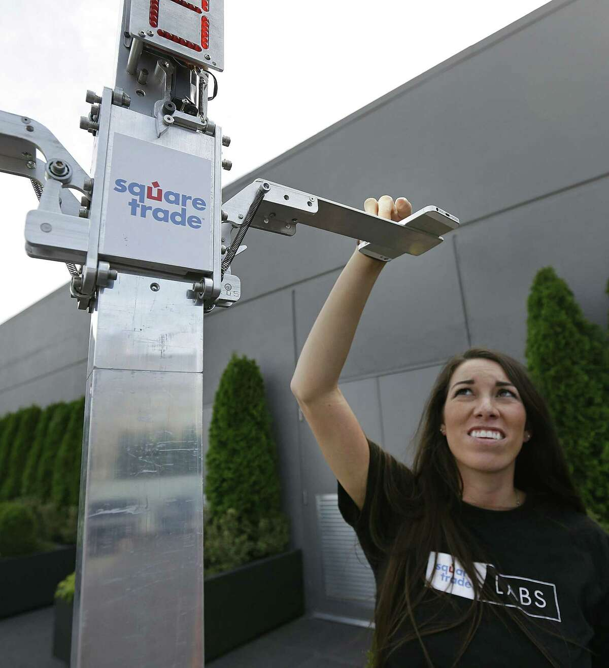 Chelsea Wickline, associate creative director at SquareTrade, places a phone atop a DropBot, a robot used to test the durability of a phone, at SquareTrade offices in San Francisco.