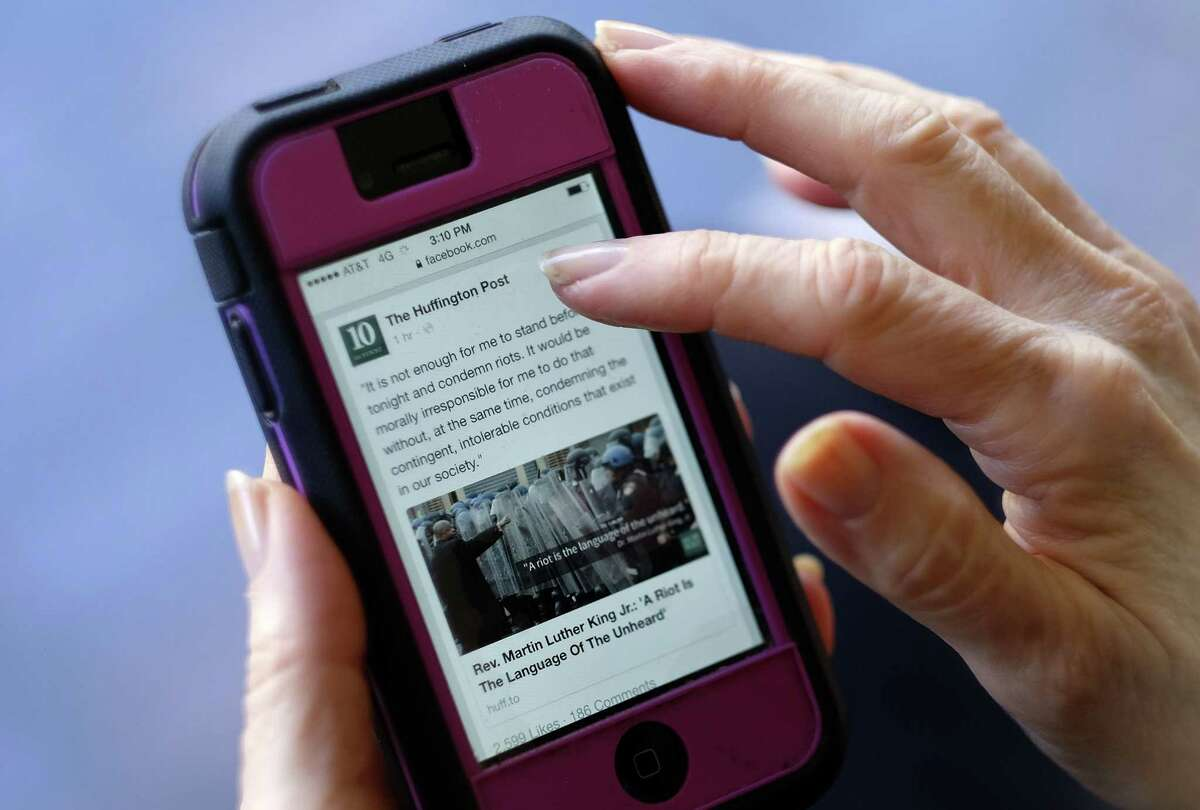 An Associated Press staffer poses using a mobile phone to read the news from The Huffington Post on Facebook, in Los Angeles.