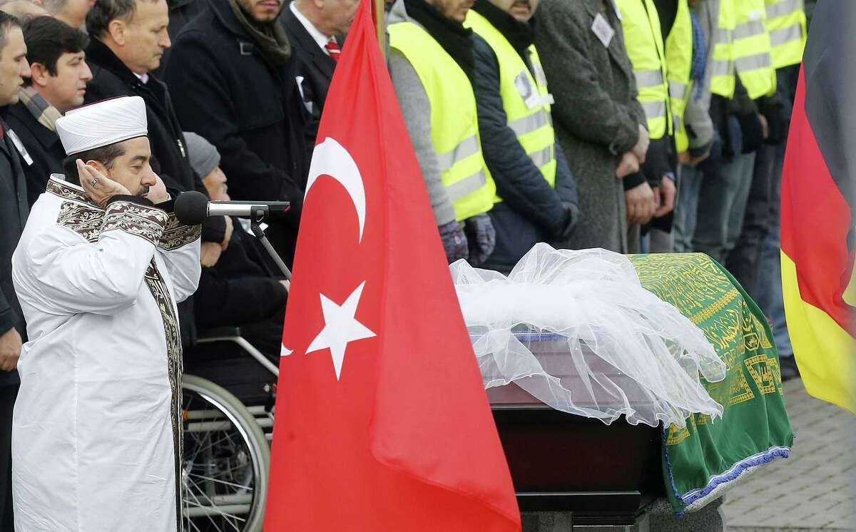 FILE - In this Dec. 3, 2014 file picture the Imam prays near the coffin withTugce Albayrak during a funeral ceremony outside a mosque in Waechtersbach, Germany. German prosecutors have indicted an 18-year-old on charges of serious bodily harm causing the death of the young woman who came to the defense of two teenage girls he and others were harassing. Teaching student Tugce Albayrak died days after being struck on the head and falling to the ground following an altercation at a McDonaldís restaurant in the city of Offenbach on Nov. 15. Offenbach prosecutor Axel Kreutz said Tuesday Feb. 3, 2015 that the suspect, identified only as Sanel M., would be tried before a juvenile court. (AP Photo/Michael Probst,file)