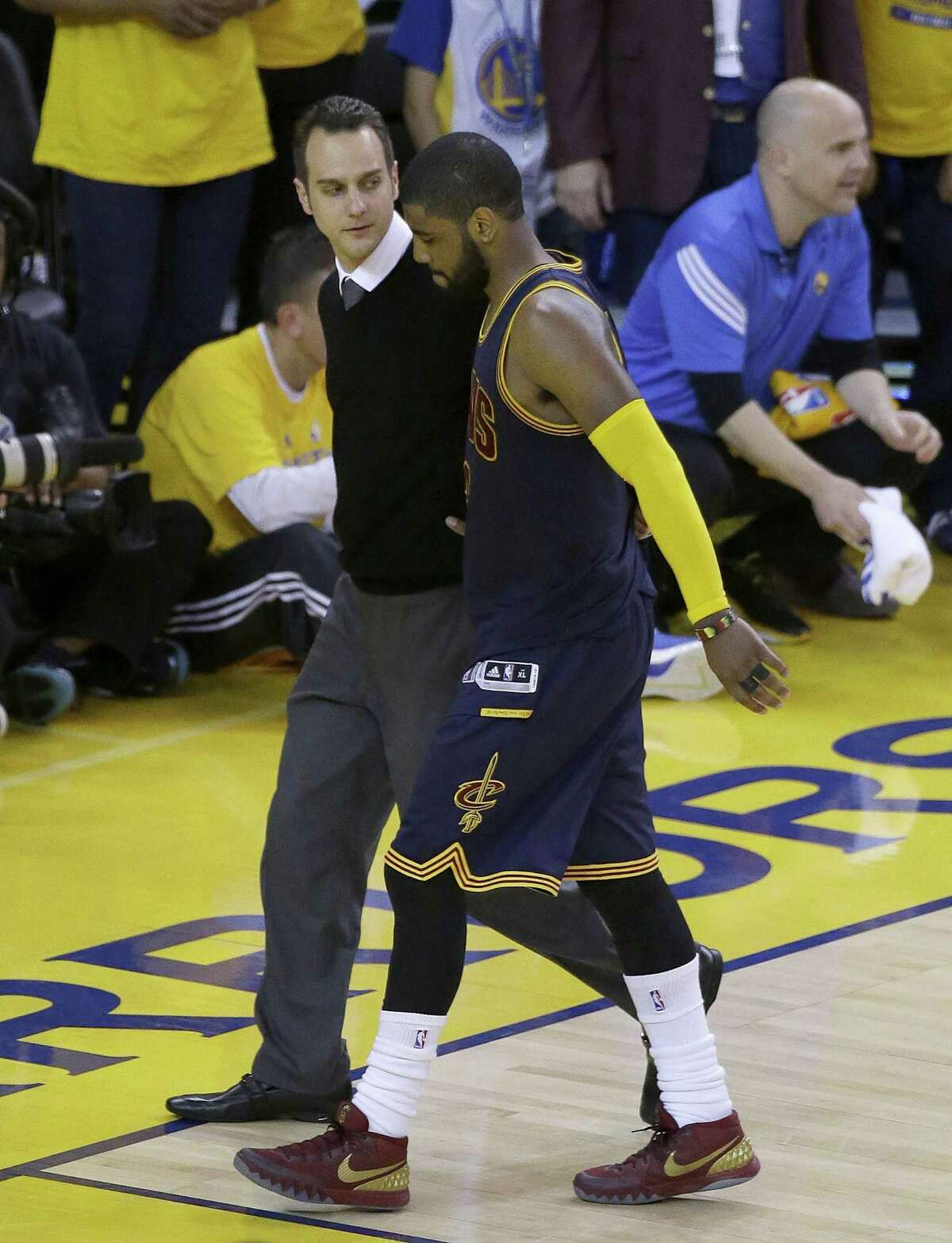 Cleveland Cavaliers guard Kyrie Irving walks off the floor after being injured during overtime of Game 1 of the NBA Finals Thursday against the Golden State Warriors in Oakland, Calif.