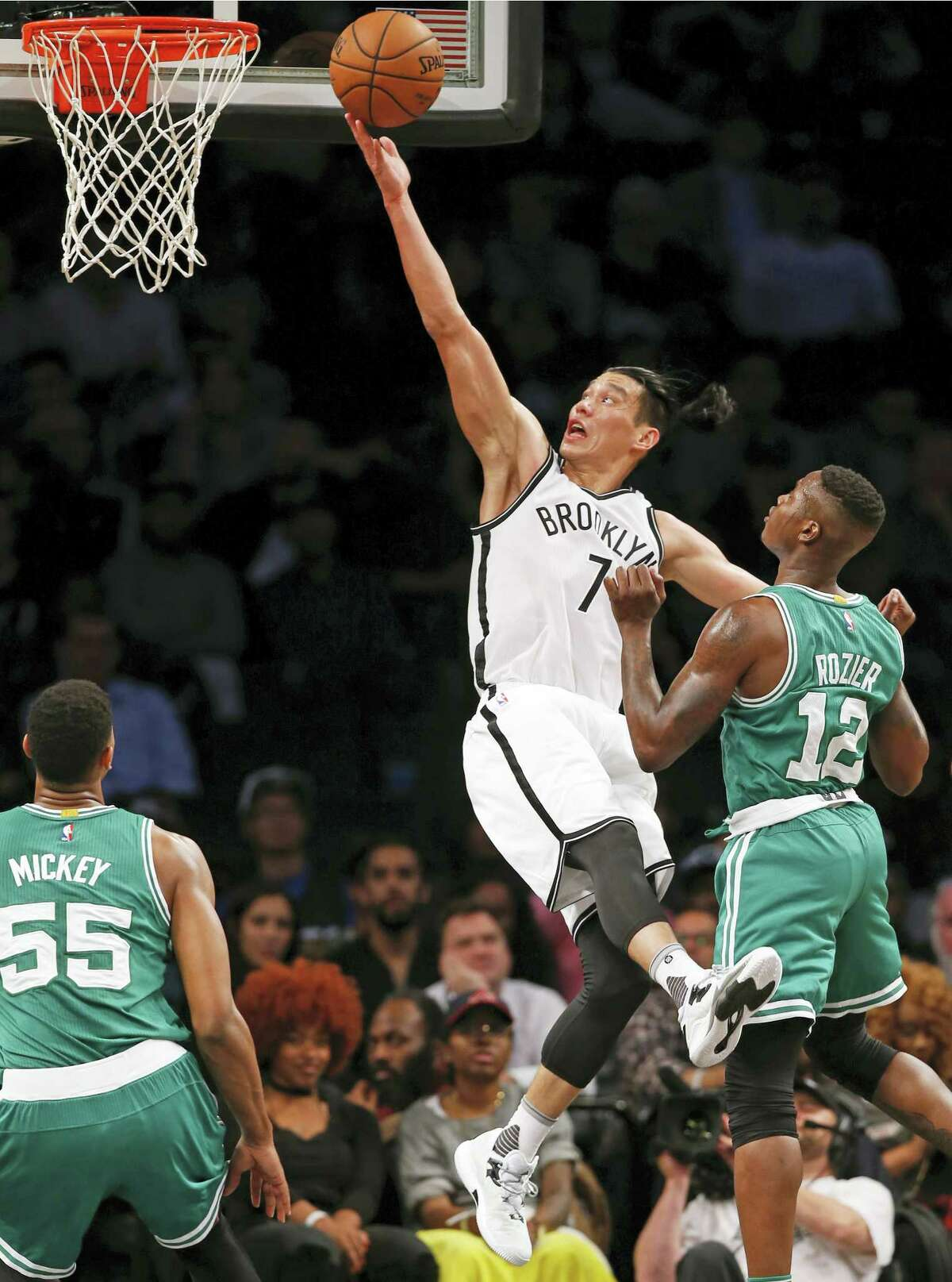 Brooklyn Nets guard Jeremy Lin (7) goes for a one-handed layup with Boston Celtics guard Terry Rozier (12) defending against him and Celtics forward Jordan Mickey (55) looking on in the second half of a preseason NBA basketball game on Oct. 13, 2016 in New York.