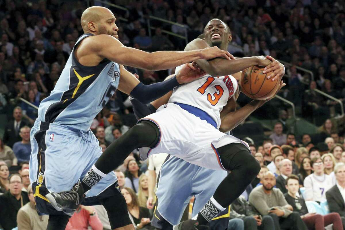 Grizzlies guard Vince Carter, left, and guard Mike Conley, in background, stop the Knicks' Jerian Grant from going to the basket during the second half on Friday.