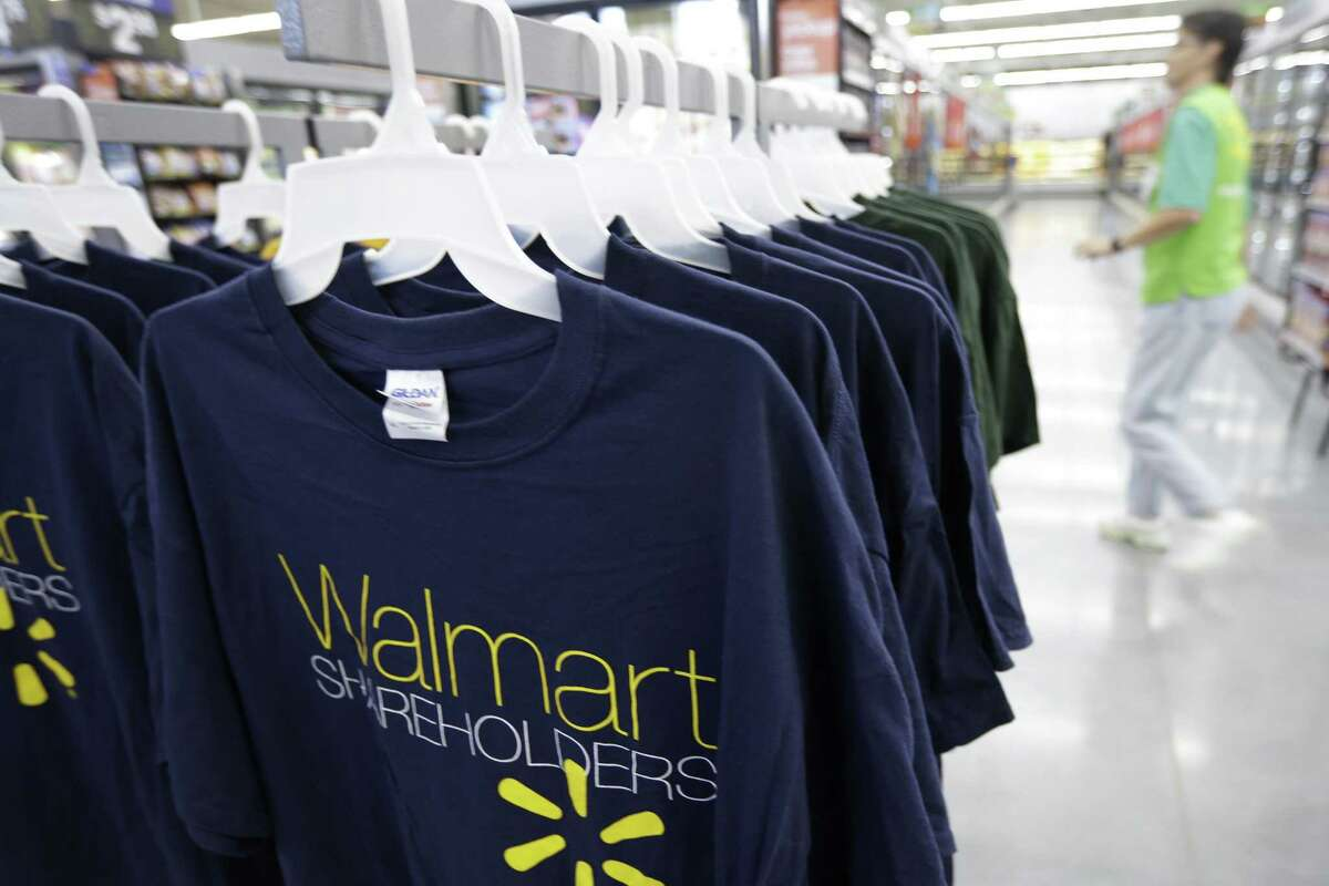 A man walks by a display of Wal-mart Shareholders shirts for sale at a Wal-mart Neighborhood Market in Bentonville, Ark., Thursday, June 4, 2015. Wal-mart shareholders and employees are gathered in northwest Arkansas for annual meeting scheduled for Friday, June 5. (AP Photo/Danny Johnston)