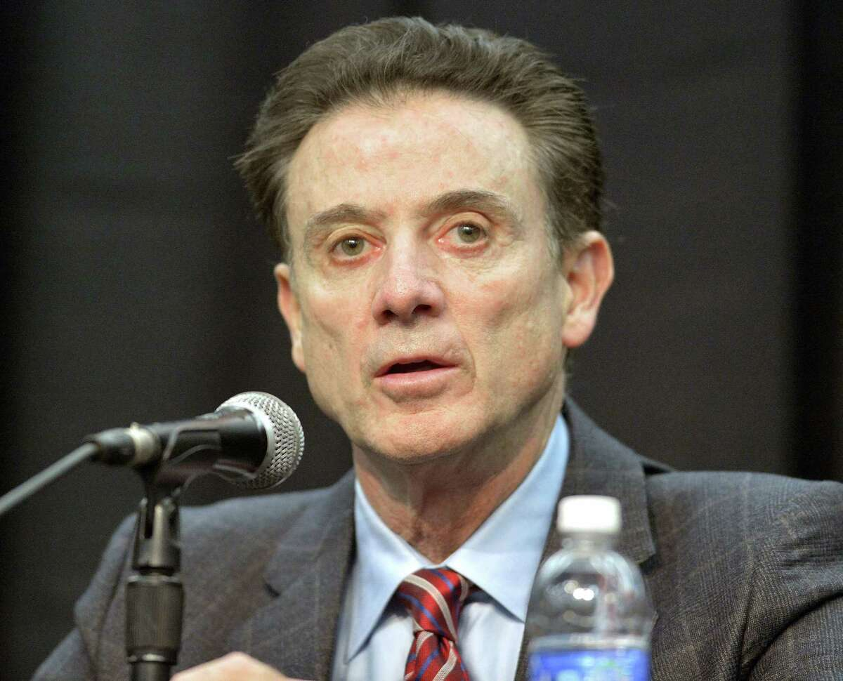 In a Feb. 5, 2016 photo, Louisville head basketball coach Rick Pitino listens to a question during a press conference, in Louisville Ky. The NCAA accuses Louisville of providing impermissible benefits and breaches of conduct as a result of its investigation into an escort's book allegations that former men's basketball staffer Andre McGee hired her and other dancers for sex parties with Cardinals recruits and players.