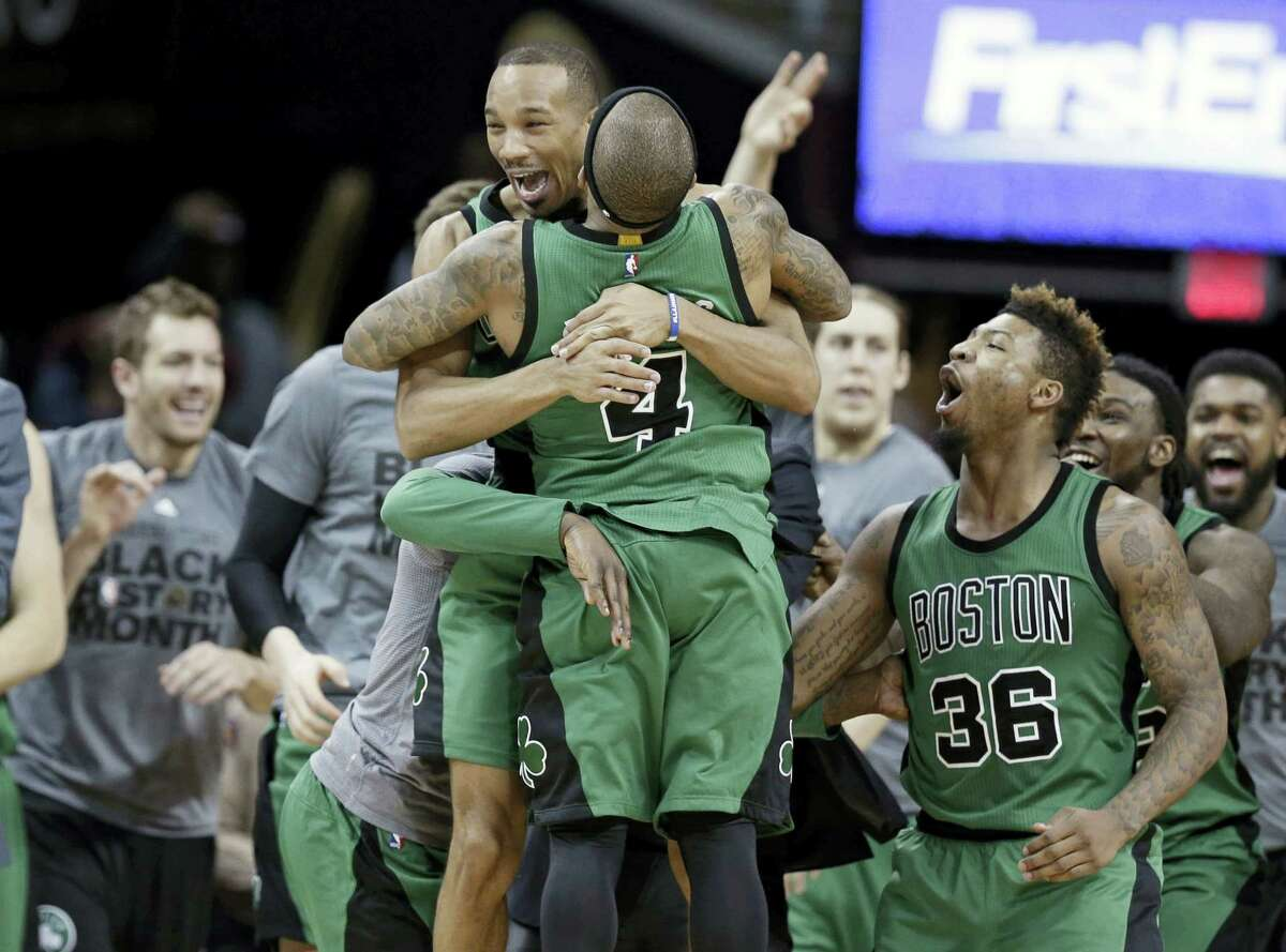 The Celtics' Avery Bradley, top, and Isaiah Thomas hug after the Celtics defeated the Cavaliers on Friday.