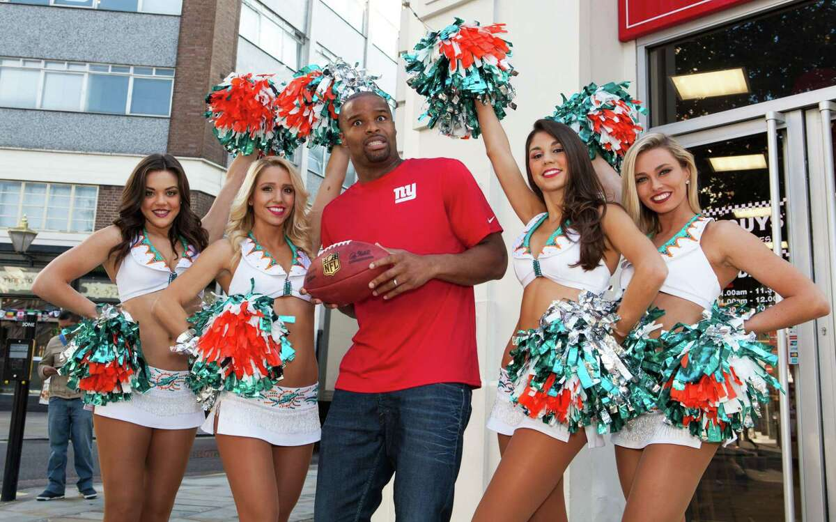 Former NFL star Osi Umenyiora, center, and Miami Dolphins Cheerleaders pose for photographers in central London on Friday.