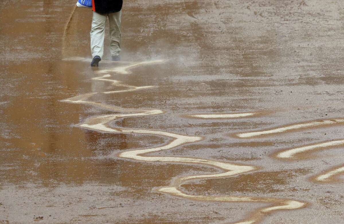 A groundskeeper tries to dry out the infield in Baltimore.
