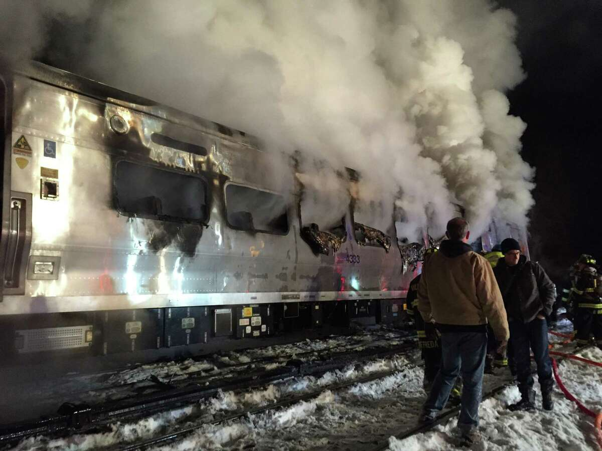 A Metro-North Railroad passenger train smolders after hitting a Jeep Cherokee in Valhalla, N.Y., Tuesday, Feb. 3, 2015.
