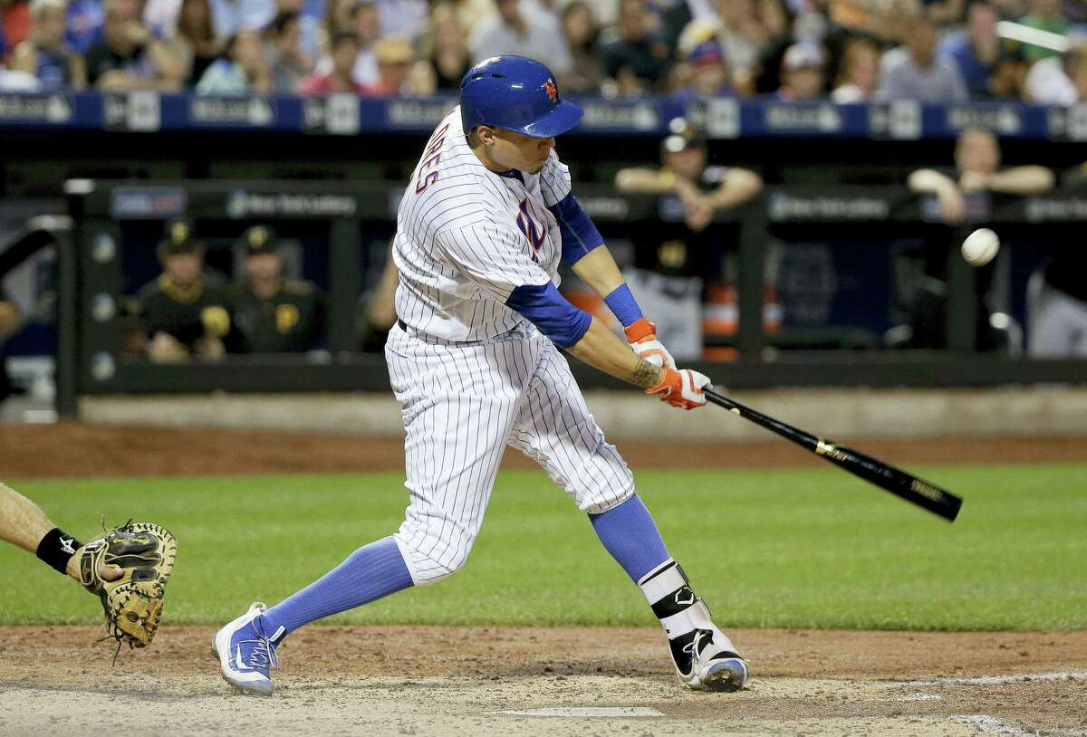 New York Mets' Wilmer Flores connects for a base hit to right field to drive in a run against the Pittsburgh Pirates during the fifth inning Wednesday in New York.