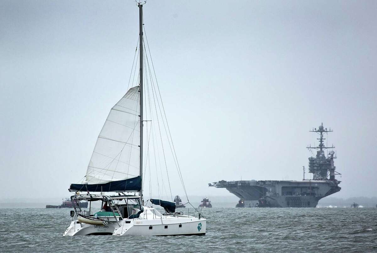 USS Harry S. Truman, CVN-75, returns to Norfolk, ahead of the approach of Hurricane Joaquin as a catamaran sails by in Hampton Va. on Thursday, Oct. 1, 2015. The approach of Hurricane Joaquin, a major Category 3 storm, set to wallop the Bahamas and move toward the U.S. could intensify the damage, but rain is forecast across the region regardless of the storm's path.