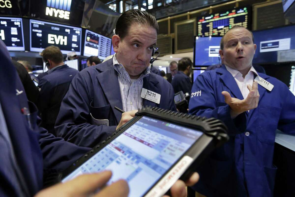 Trader Tommy Kalikas, center, works on the floor of the New York Stock Exchange Friday.