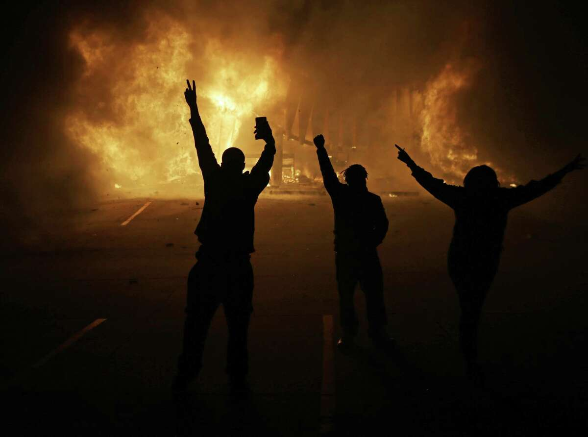 In this Nov. 25, 2014, file photo, people watch as stores burn in Ferguson, Mo., after a grand jury decided not to indict Ferguson police Officer Darren Wilson in the death of Michael Brown, the unarmed, black 18-year-old whose fatal shooting sparked sometimes violent protests. The U.S. Department of Justice on Friday, Oct. 2, 2015, will release the findings of the last of its third and final review stemming from the unrest in Ferguson.