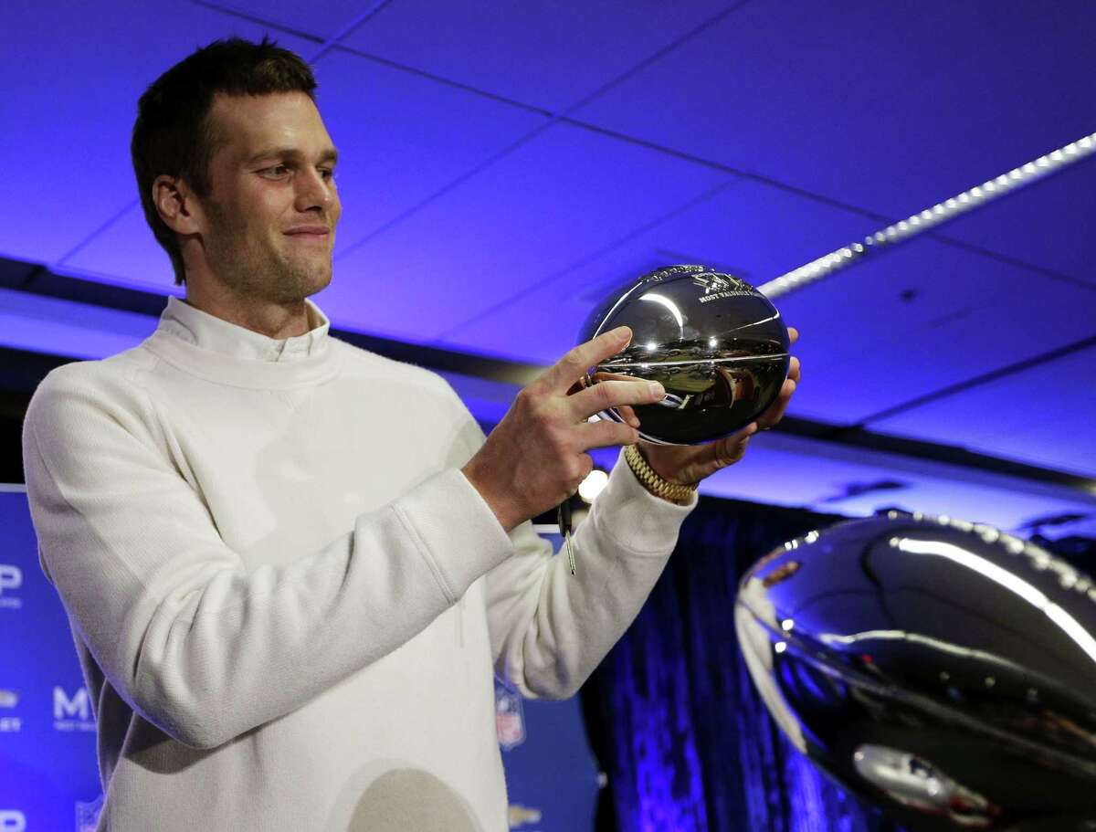 New England Patriots quarterback Tom Brady holds up his Pete Rozelle Trophy during a news conference.