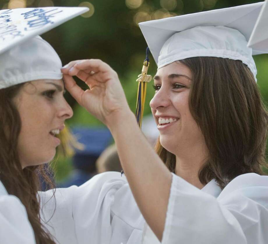 Valerie Preville has her hat adjusted by Alanna Poppe during the Brookfield High School graduation at the O'Neil Center. Saturday, June 19, 2010 Photo: Scott Mullin / The News-Times Freelance