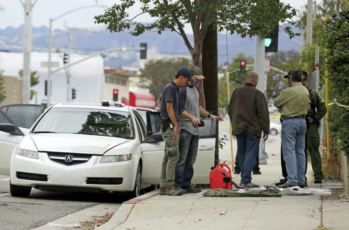 Investigators view items removed from a car, left, after a heavily armed man was arrested in Santa Monica, Calif., early Sunday, June 12, 2016. The man reportedly told police he was in the area for West Hollywood's huge gay pride parade. Authorities did not know of any connection between the gay nightclub shooting in Orlando, Fla., early Sunday and the Santa Monica arrest.