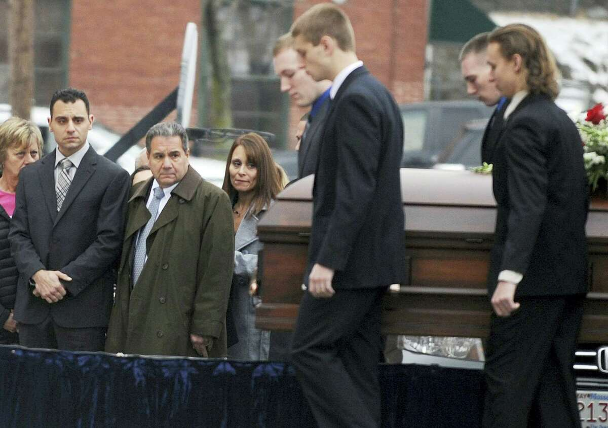 In this Dec. 30, 2015 photo, Richard Dabate, left, watches the casket bearing his late wife Connie Dabate being carried during her funeral outside St. Bernard Roman Catholic Church in Vernon. While responding to a burglary alarm on Dec. 23, authorities found Connie Dabate, mother of two children, shot to death and her husband Richard Dabate injured inside their Ellington home. No arrests have been made, leaving local residents concerned and speculating.