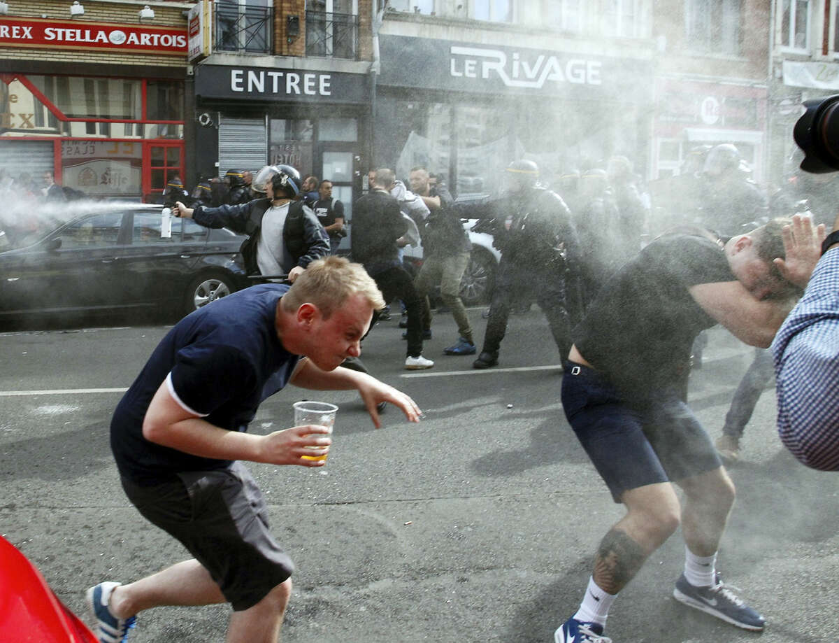 English fans run after getting sprayed with pepper spray by French police during scuffles in downtown Lille, northern France, Wednesday, June 15, 2016, one day ahead of the Euro 2016 Group B soccer match against Wales in nearby Lens. Russia were playing Slovakia at the Pierre Mauroy stadium in Villeneuve d'Ascq, near Lille on Wednesday which raised the possibility of violence after clashes between supporters from the two countries at their previous match in Marseille last weekend.