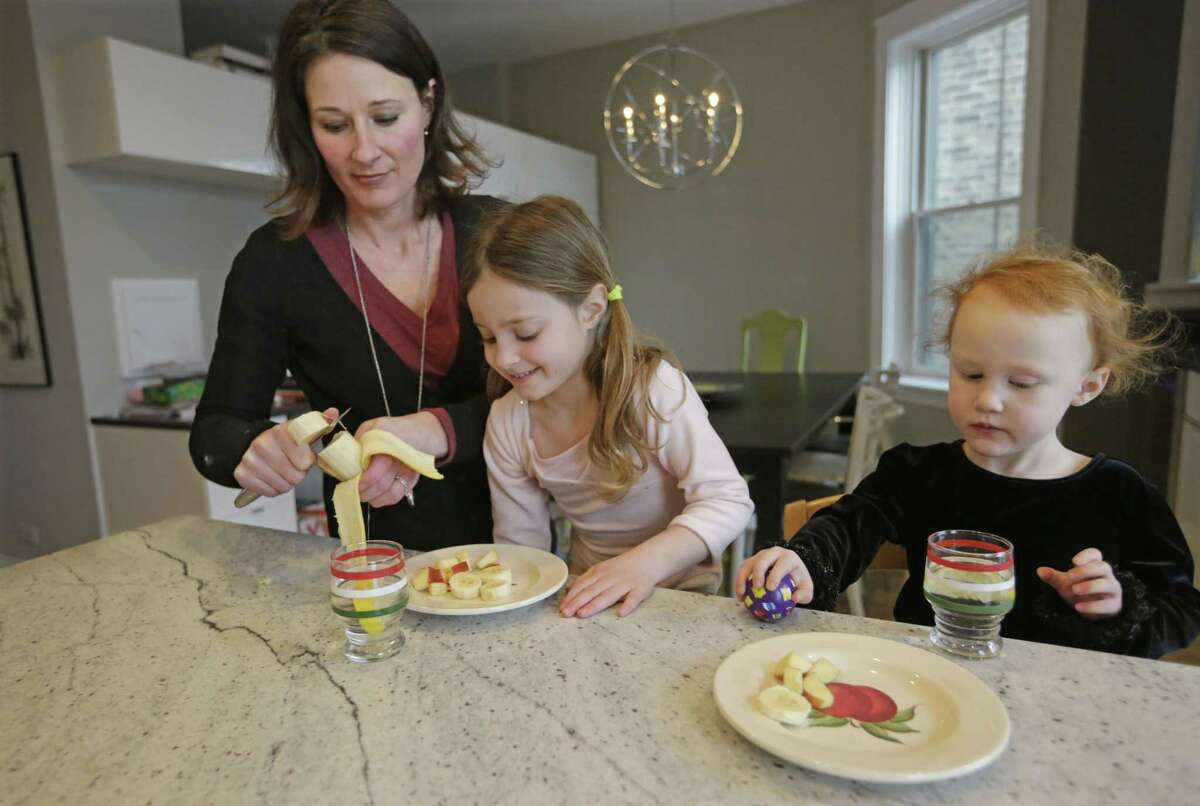 Kathy Burnett prepares a snack for her daughters Claudia, center, and Sabina right, after their gymnastics class Thursday, Jan. 29, 2015, in Chicago. Burnett says she tries to feed her girls healthy, natural foods rather than commercial packaged products.