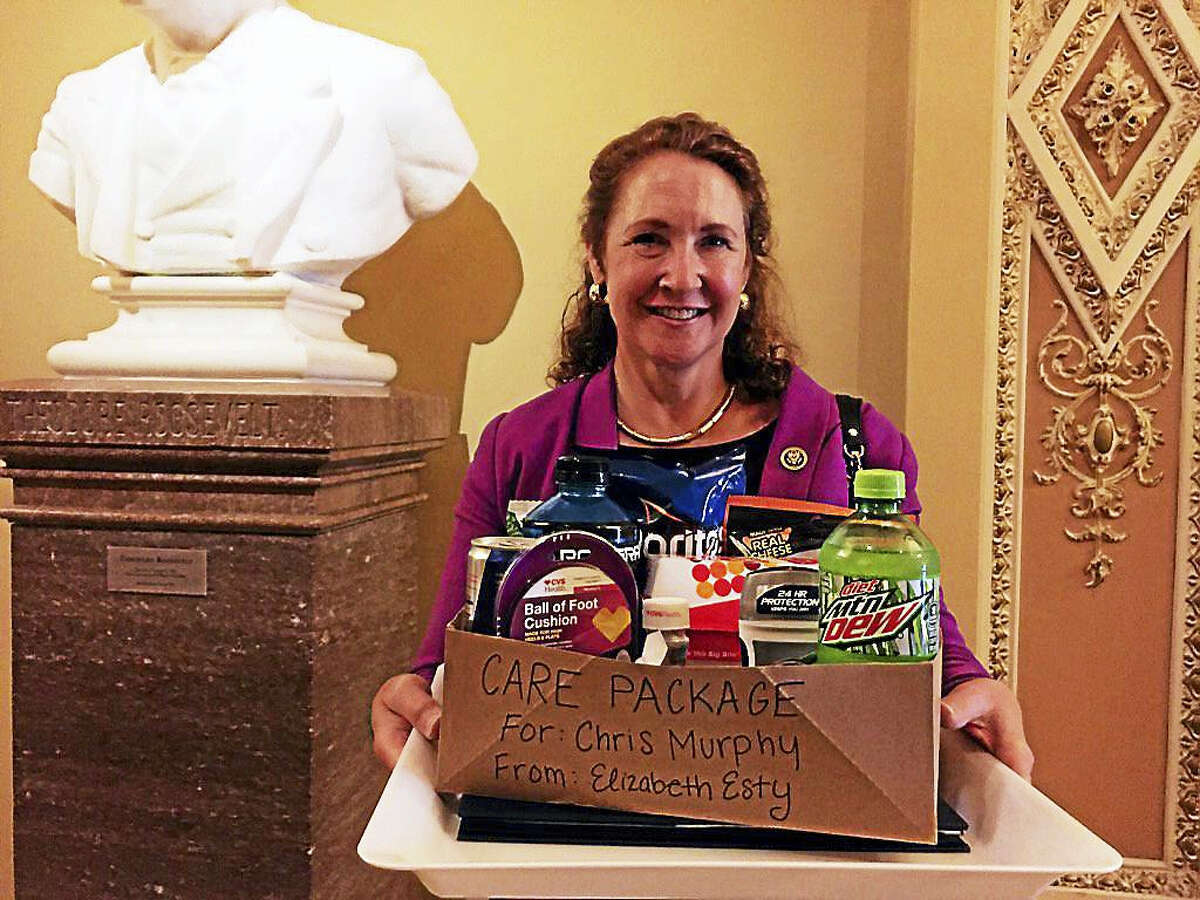 U.S. Rep. Elizabeth Esty, D-5, smiles as she carries what she tweeted was a care package for U.S. Sen. Chris Murphy on the Senate floor, where he launched a filibuster to force a vote on gun control legislation.