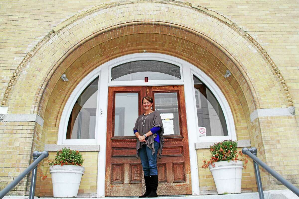 Karin Taylor, library services director for Beardsley and Memorial Library, stands on the building's front steps on Munro Place beneath the crumbling, ornamental arch that is undergoing repair.