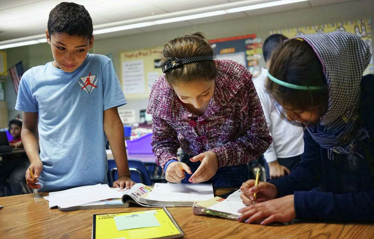 In this Oct. 4, 2016 photo, Abdulhamid Ashehneh, 12, works on English language exercises with fellow students in a class filled with refugee children at Cajon Valley Middle School in El Cajon, Calif. According to the U.S. State Department, nearly 80 percent of the more than 11,000 Syrian arrivals over the past year were children. Many of those children are enrolling in public schools around the country, including Chicago; Austin, Texas; New Haven, Connecticut; and El Cajon, which received 76 new Syrian students the first week of school.