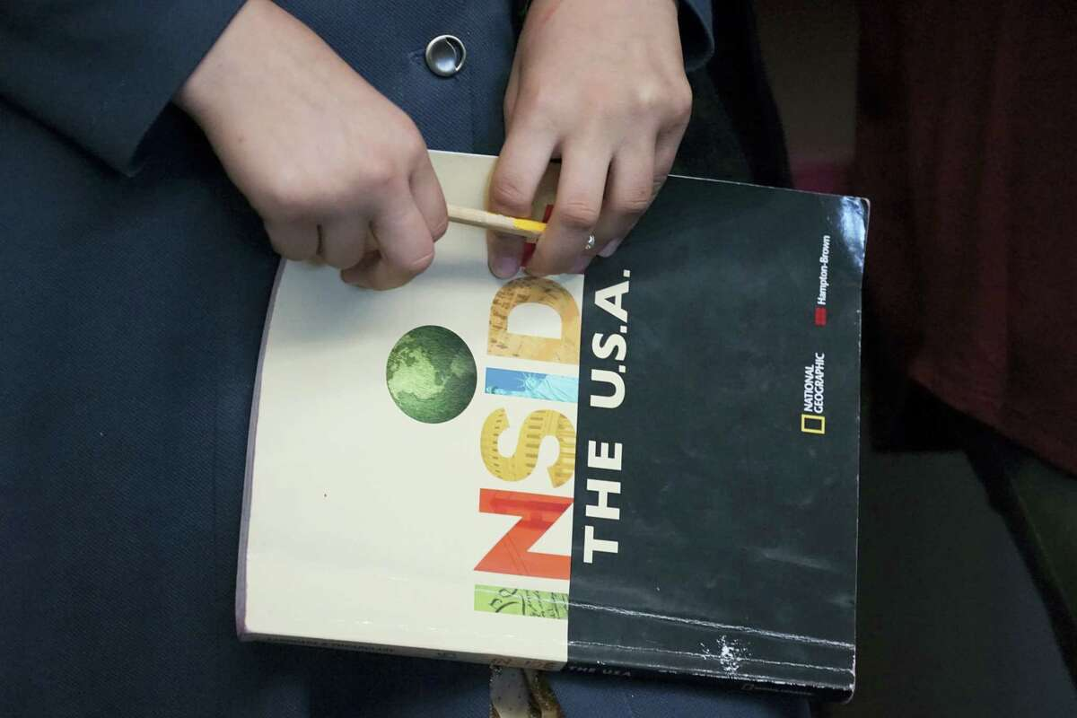 """In this Tuesday, Oct. 4, 2016 photo, a student holds an """"Inside the USA"""" textbook in a class filled with refugee children at Cajon Valley Middle School in El Cajon, Calif. According to the U.S. State Department, nearly 80 percent of the more than 11,000 Syrian arrivals over the past year were children. Many of those children are enrolling in public schools around the country, including Chicago; Austin, Texas; New Haven, Connecticut; and El Cajon, which received 76 new Syrian students the first week of school. (AP Photo/Christine Armario)"""