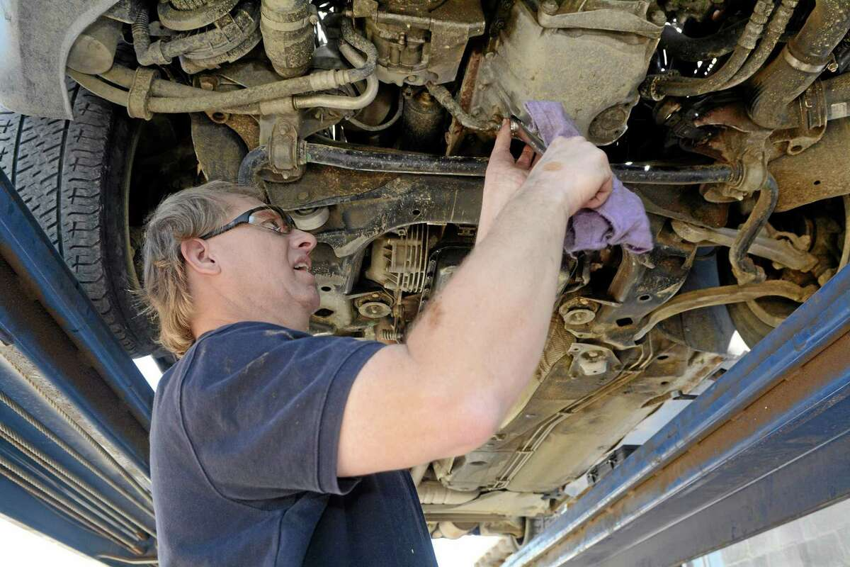 Cliff Alderson, of Alamagordo, N.M., loosens a bolt to let oil pour out during an oil change on a car.