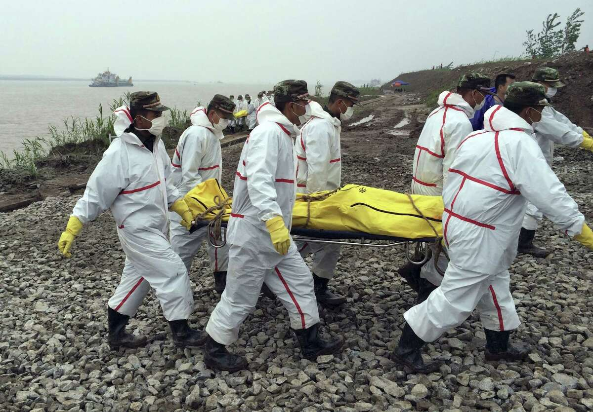 Rescue workers carry a body recovered from a capsized cruise ship in the Yangtze River in Jianli county in southern China's Hubei province Thursday, June 4, 2015. Rescuers cut three holes into the overturned hull of the river cruise ship in unsuccessful attempts to find more survivors Thursday. (Chinatopix Via AP) CHINA OUT