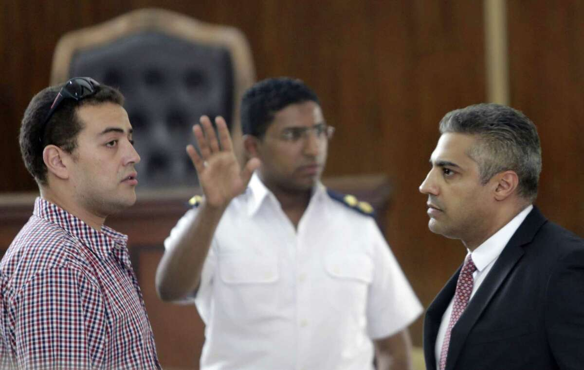 An Egyptian policeman directs Canadian Al-Jazeera English journalist Mohammed Fahmy, right, and his Egyptian colleague Baher Mohammed, left, as they wait for their retrial in front of a policeman at a courtroom in Tora prison, in Cairo, Egypt.