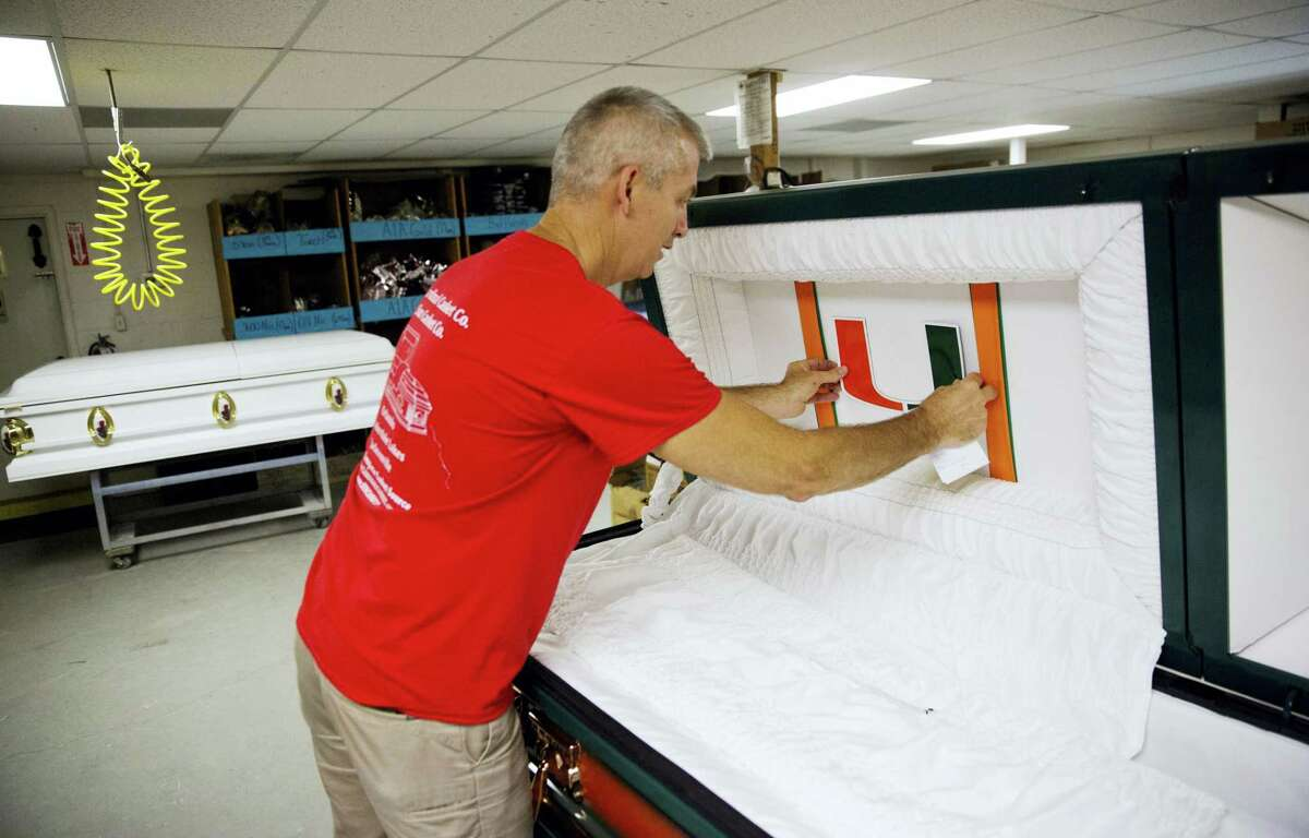 """Kelly Greenwood, co-owner of Cardinal Casket Company, places a University of Miami magnet inside a casket for a victim of the Pulse nightclub shooting who was also a fan of the university in preparation for the funeral Wednesday, June 15, 2016, in Orlando, Fla. """"It hits you, it hits everyone here,"""" said Greenwood who lost a friend in the shooting. """"I feel proud knowing that I made something for my friend's mother that will be with them the last time their family sees him."""" The locally owned company has so far received orders for 23 caskets ahead of the upcoming funerals for the victims."""