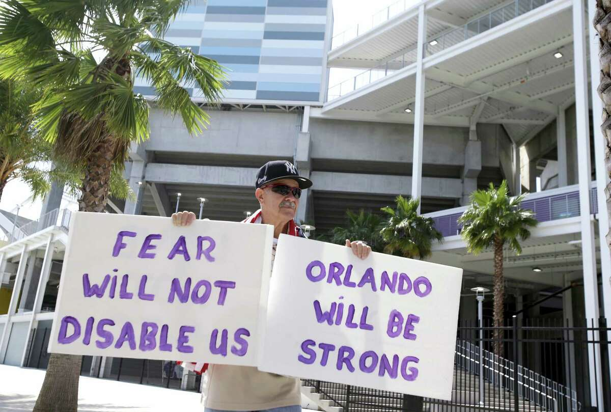 Andy Garcia, walks around Camping World Stadium, holding signs in support of the victims of the recent mass shootings and their families at the Pulse nightclub on June 15, 2016, in Orlando, Fla. The stadium opened an assistance center for victims and their families today.