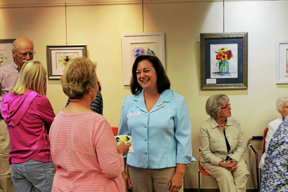 The new director of the Harwinton Library, Alice Frelier, talks to visitors at Wednesday's event.