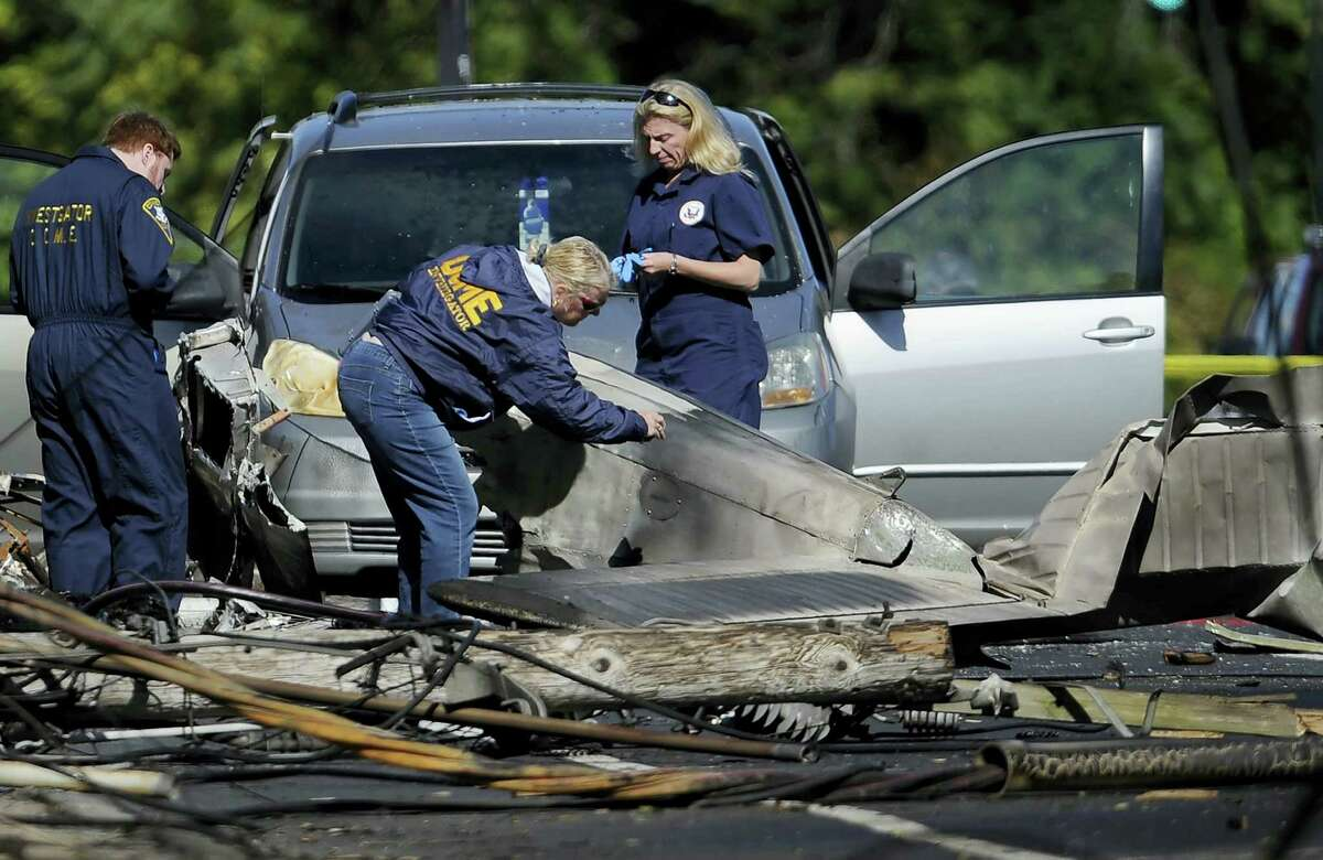 Investigators look at the remains of a small plane along Main St. in East Hartford a day following the plane's crash.