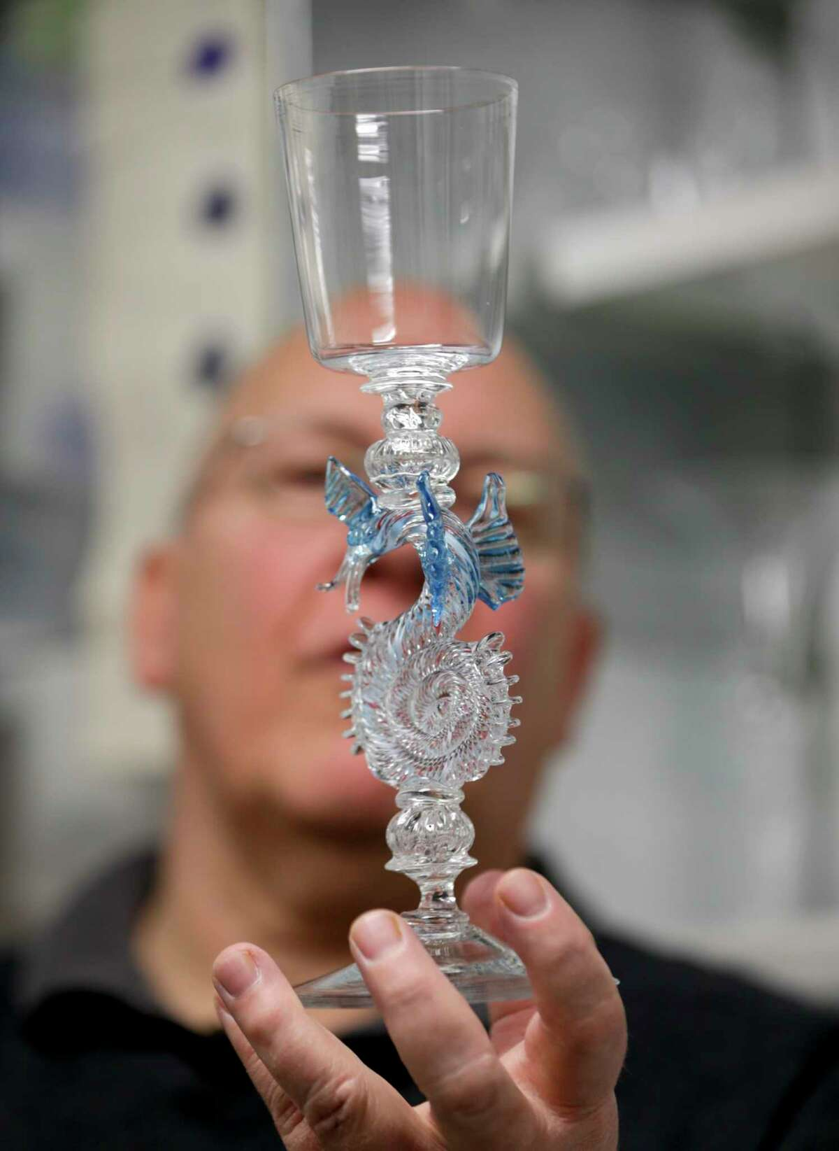In this Friday, Jan. 22, 2016 photo, glassblower William Gudenrath holds a dragon-stem goblet at the Corning Museum of Glass in Corning, N.Y.. Gudenrath spent decades researching how Renaissance-era glassmakers produced objects that are now considered works of art.