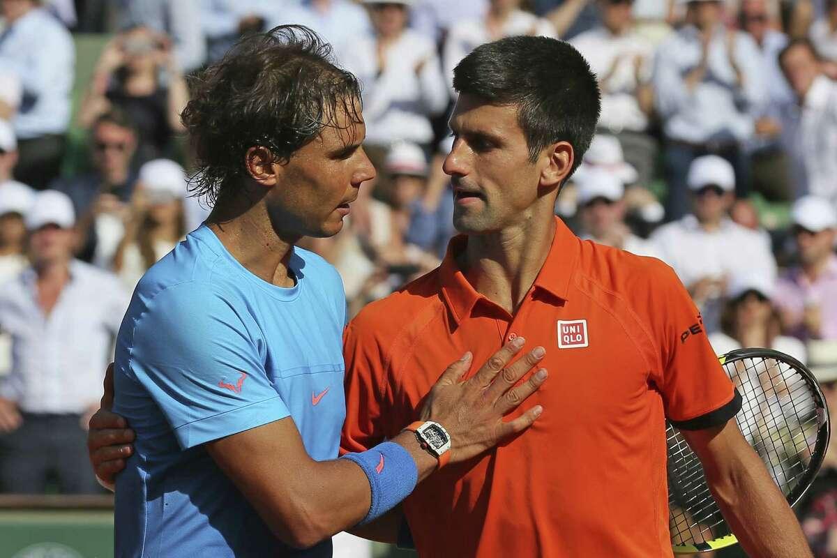 Novak Djokovic hugs Rafael Nadal, left, after winning their quarterfinal match at the French Open 7-5, 6-3, 6-1 at the Roland Garros stadium in Paris.