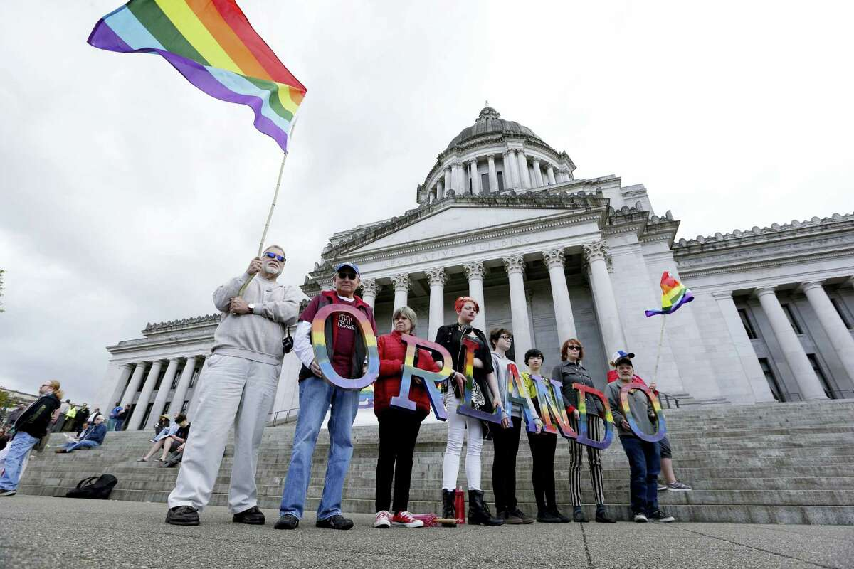"""Members of Capital City Pride and others from the LGBT community hold up letters spelling out """"Orlando"""" to honor of the recent shooting at a gay nightclub days earlier before the raising of a rainbow flag in front of the Washington state Capitol, Wednesday, June 15, 2016, in Olympia, Wash. The rainbow flag was raised to mark the start of Gay Pride month, and was immediately lowered to half-staff to mark last weekend's mass shooting at a central Florida nightclub."""