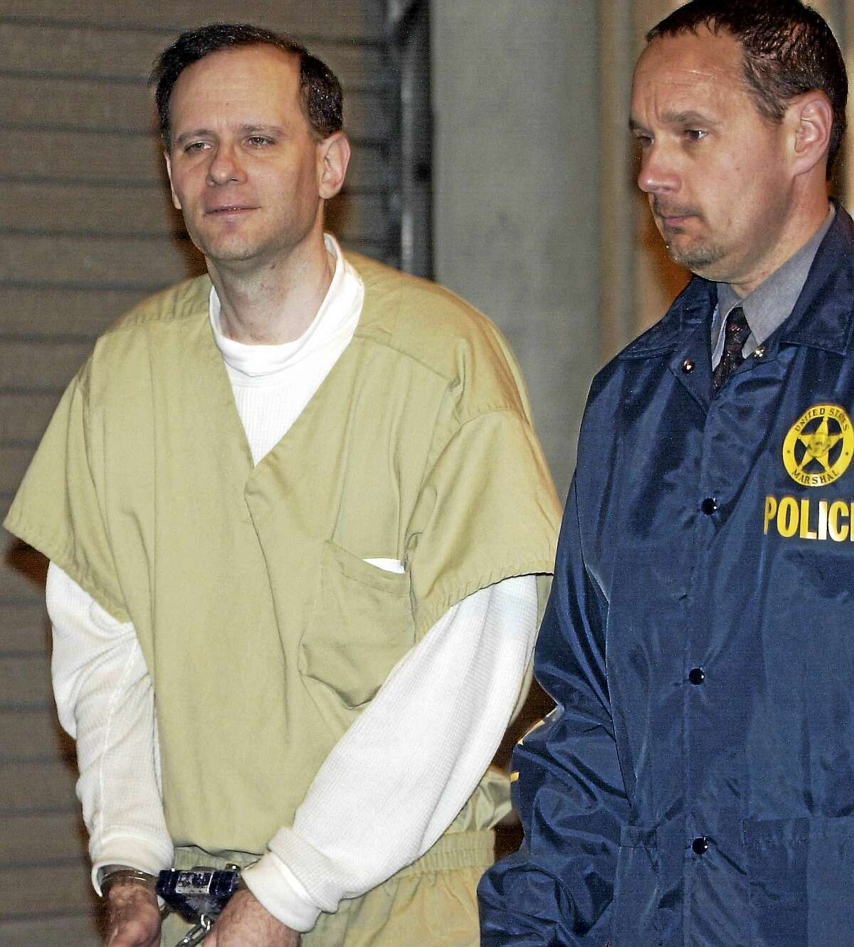 In this May 15, 2002 file photo, Martin Frankel, a financier accused of stealing more than $200 million from insurance companies, is escorted from U.S. District Court in New Haven, Conn. Frankel was sentenced in 2004 to 17 years behind bars, and released to a halfway house in September 2015. Frankel is due back in New Haven federal court on Oct. 1, 2015, less than a month after getting out of prison, charged with violating the terms of his release.