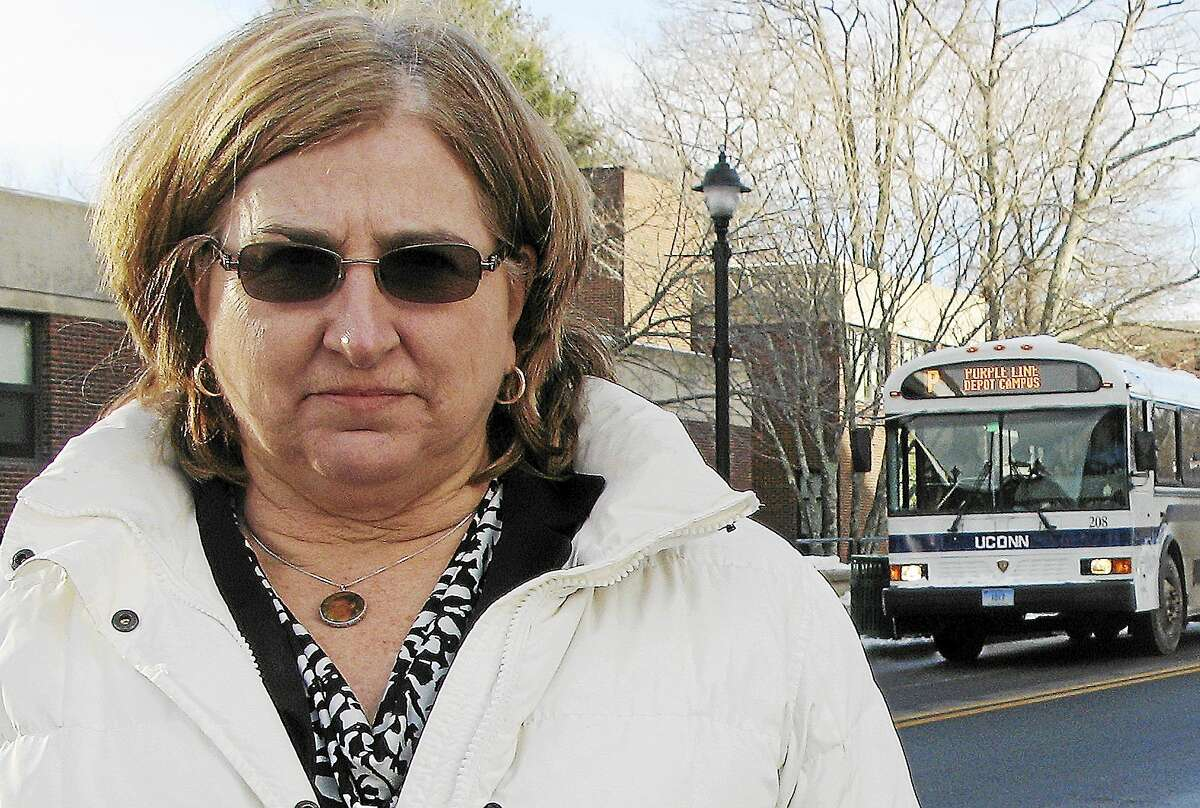 In this Jan. 29, 2015 photo, Linda Plamondon of Westminster, Mass., poses near a UConn transit bus on Hillside Road on the school's campus in Storrs, Conn. Plamondon, whose son David was struck and killed by a bus on campus in 2011, is pushing for reforms to the school's bus system.