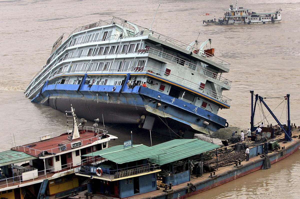 FILE - In this file photo taken Sept. 1, 2005, rescue workers try to pull a stranded Yangtze River cruise ship which has ran aground due to heavy fog in Chongqing, China. For centuries, the Yangtze was the key route for transporting goods in China, but parts of its waters were dangerous for junks to navigate because of rocks and fluctuating water levels.(EyePress via AP, File )