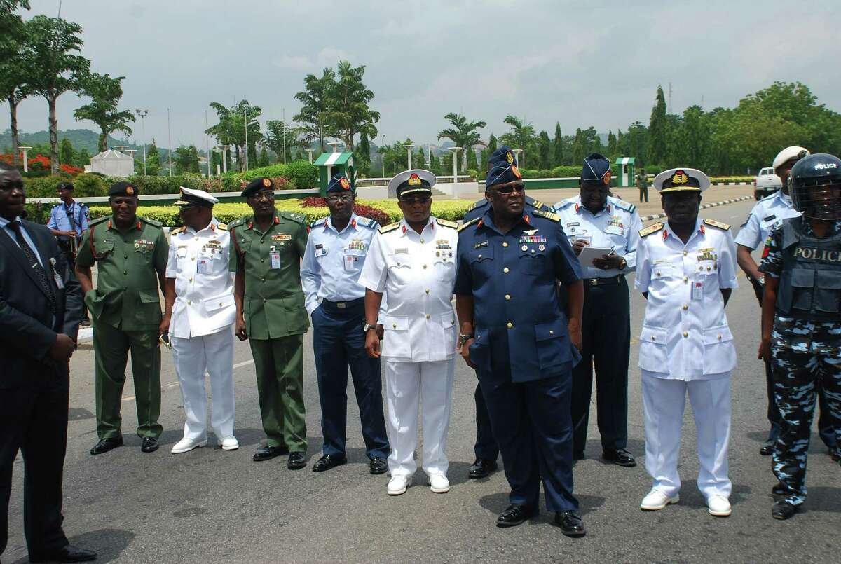 FILE - In this Monday, May. 26, 2014 file photo, Nigeria's chief of defense staff Air Marshal Alex S. Badeh, foreground third right, and other military chiefs wait to address the Nigerians Against Terrorism group during a demonstration calling on the government to rescue the kidnapped girls of the government secondary school Chibok, in Abuja, Nigeria. Nigerian military abuses caused the deaths of some 8,000 people in the fight against Boko Haram extremists, Amnesty International said Wednesday, June. 3, 2015 in a report naming senior officers it wants investigated for alleged war crimes. (AP Photo/Olamikan Gbemiga File)