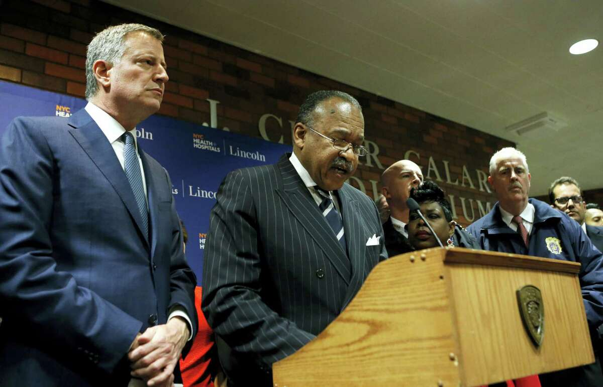 New York City Mayor Bill de Blasio listens as New York City Police First Deputy Commissioner Benjamin Tucker speaks at a hastily called press conference at Lincoln Hospital, Thursday, Feb. 4, 2016, in the Bronx borough of New York after two New York City police officers were shot in a public housing complex int he Bronx by an armed suspect who apparently turned the weapon on himself not far from wherede Blasio was delivering his state of the city address Thursday evening. New York Police Department Chief of Department James P. O'Neill, listens, far right.