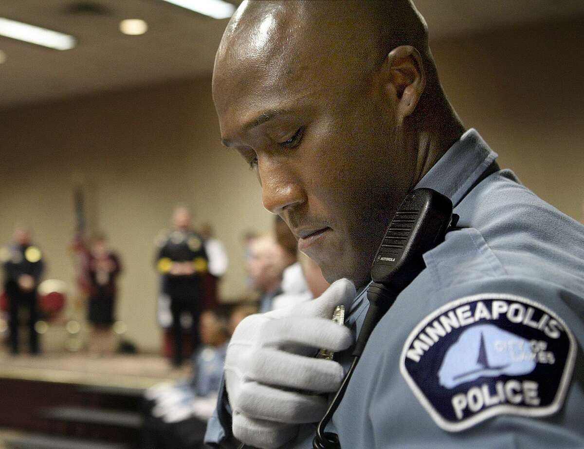 In this March 15, 2007, photo, Minneapolis Police Department Academy graduate Michael Griffin pins his badge onto his uniform during a graduation ceremony in Minneapolis. An indictment May 20 accuses Griffin of assaulting several people while off-duty and filing false reports.