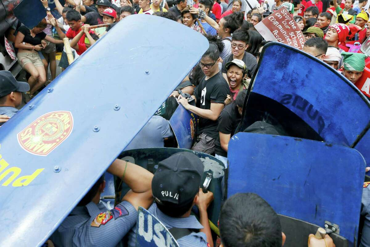 Police and protesters clash during a violent protest outside the U.S. Embassy in Manila, Philippines, Wednesday, Oct. 19, 2016. A Philippine police van rammed into protesters, leaving several bloodied, as an anti-U.S. rally turned violent Wednesday at the embassy in Manila.